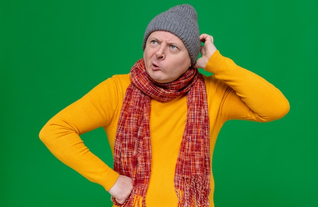 Confused adult man with winter hat and scarf around his neck scratching his head and looking at side