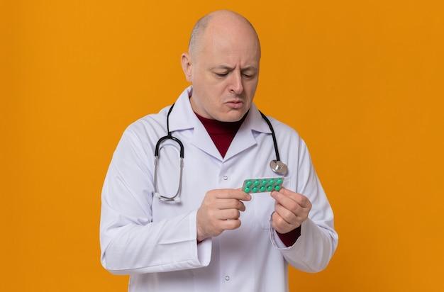 청진기를 들고 약 물집 팩을 보고 있는 의사 유니폼을 입은 혼란스러운 성인 슬라브 남자
