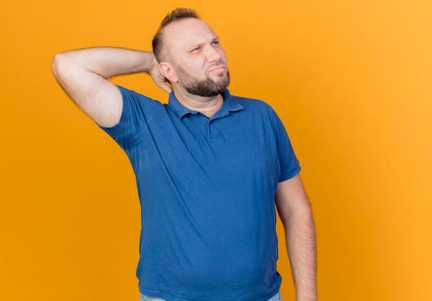 Uomo slavo adulto confuso che esamina lato tenendo la mano dietro il collo isolato sulla parete arancione con lo spazio della copia