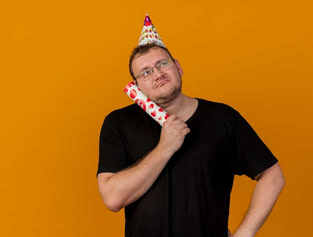 Confused adult slavic man in optical glasses wearing birthday cap holds confetti cannon looking at side
