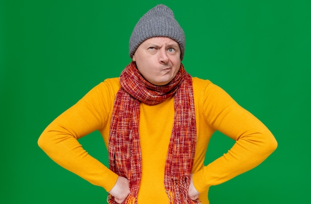 Confused adult slavic man with winter hat and scarf around his neck putting hands on his waist and looking at side