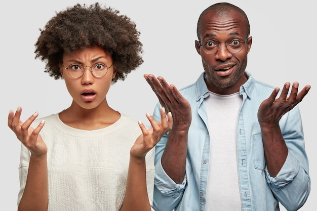 Confused african american couple gesture together with puzzlement, being displeased with conditions in hotel where they going to stay, have clueless expressions, isolated over white wall