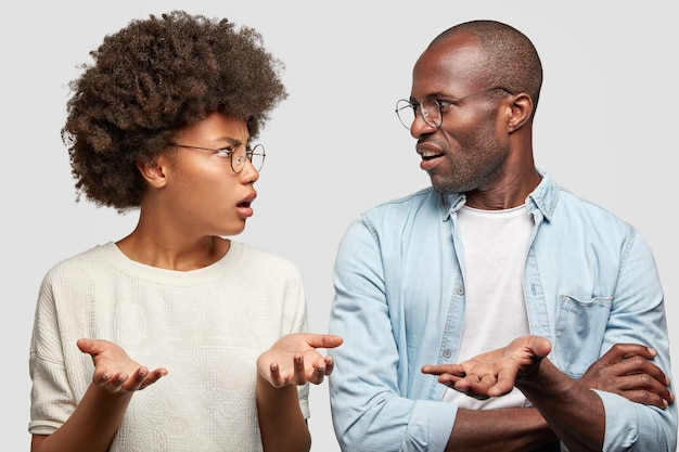 Confused african american couple look at each other angrily, clasp hands, don`t know where their money disappeared, wear round spectacles, isolated over white wall. family has problems