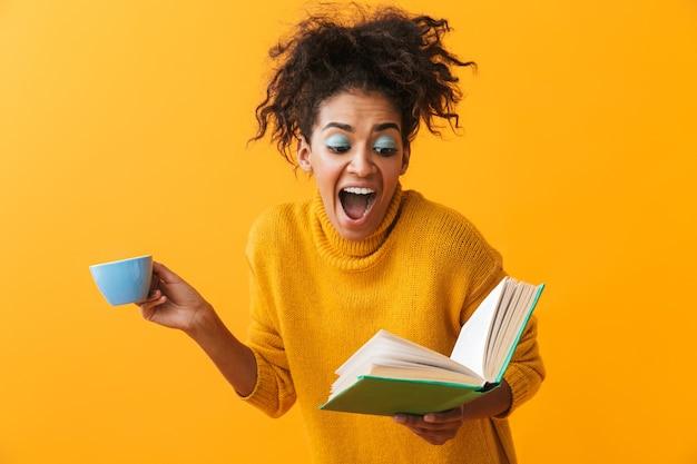 고립 된 서, 책을 읽고, 커피를 마시는 스웨터를 입고 혼란 된 아프리카 여자