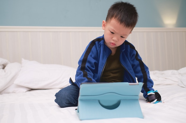 Confused aggressive asian 3 - 4 years old toddler boy child sitting in bed watching a video , playing game from tablet pc, kids playing with tablet computer, gadget-addicted children concept