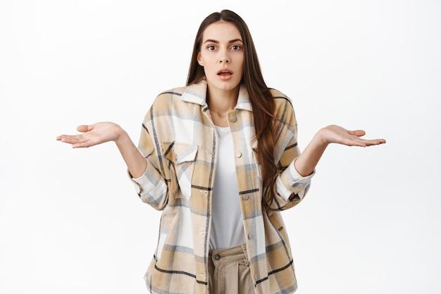 混乱して無知な女性が頭を振って肩をすくめる、困惑しているように見える、わからない、何も知らない、白い壁の上に立っている