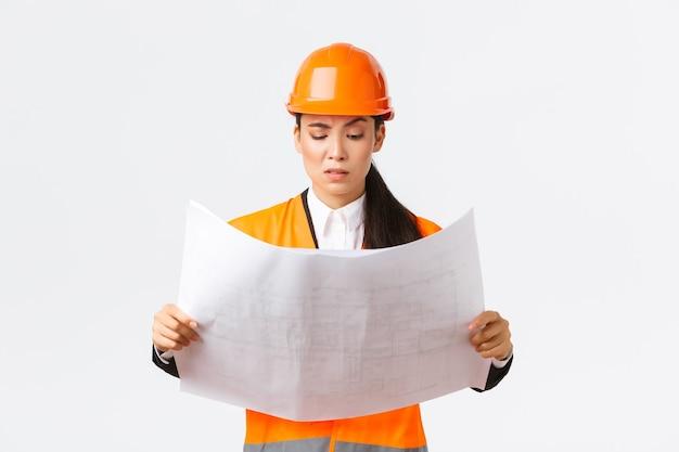 Смущенная и сомнительная азиатская женщина-главный инженер, ведущий архитектор на строительной площадке, недовольная и нерешительная при взгляде на странные чертежи, чтение сбивающего с толку строительного проекта, белый фон