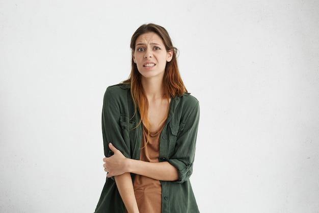 髪を染めた髪と健康な肌を持つ困惑した眉をひそめている女性は、困惑した表情で何を選ぶべきかわからないままカジュアルに服を着ました。否定的な感情を表現するヨーロッパの女性