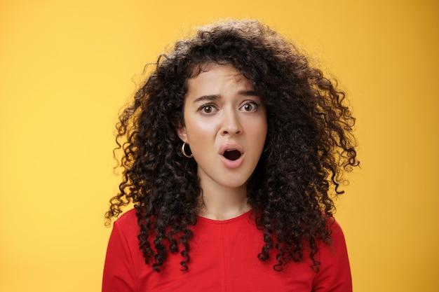 混乱し、欲求不満の若い質問された女性は、巻き毛が口を開け、眉を上げて、黄色の背景に無知で動揺している不公平な状況に不満を抱いています。