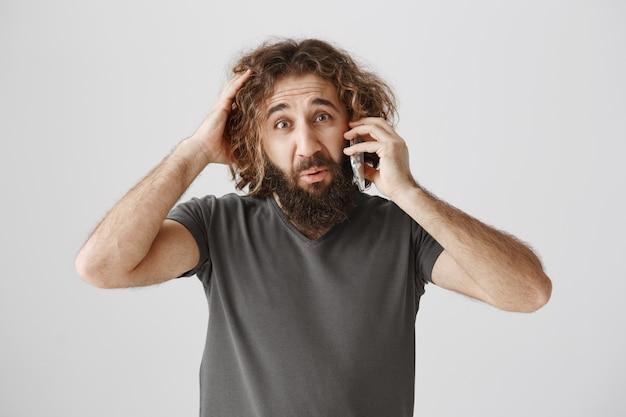 Смущенный и нерешительный парень с ближнего востока разговаривает по телефону и выглядит нерешительным