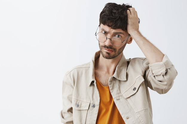 Смущенный и нерешительный стильный бородатый парень позирует у белой стены