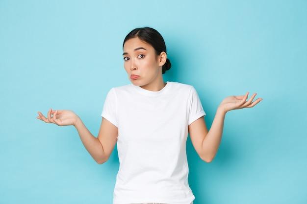 Смущенная и нерешительная милая азиатская девушка гримасничает, не понимая чего-то, поднимает руки невежественно и недоуменно пожимает плечами, ничего не знает, стоит у синей стены