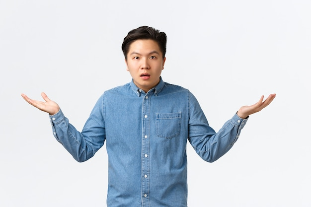 셔츠를 입은 혼란스럽고 어리둥절한 아시아 남성은 무슨 일이 일어나고 있는지 이해하지 못하고, 손을 옆으로 들고 어깨를 으쓱하고, 설명을 기다리고, 궁금해하고, 질문을 받고 흰색 배경에 서 있습니다