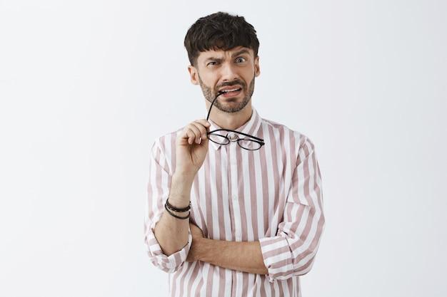 Смущенный и озадаченный стильный бородатый парень позирует на фоне белой стены в очках