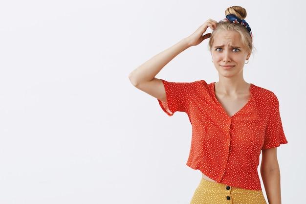 Смущенная и озадаченная молодая блондинка позирует у белой стены