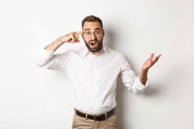혼란스럽고 충격적인 남자가 머리를 가리키고, 어리석은 행동을하고 흰색으로 서서 직원을 꾸짖습니다.