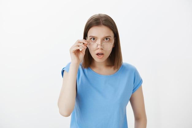 Смущенная и шокированная женщина снимает очки, удивленно смотрит
