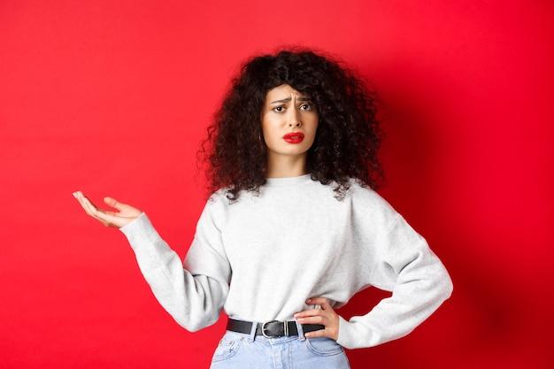 곱슬 머리를 가진 혼란스럽고 회의적인 여성, 눈살을 찌푸리고 손을 들어 의문을 제기하고 이상한 것을 이해할 수 없으며 빨간 벽에 서 있습니다.