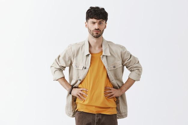 Смущенный и подозрительный стильный бородатый парень позирует у белой стены