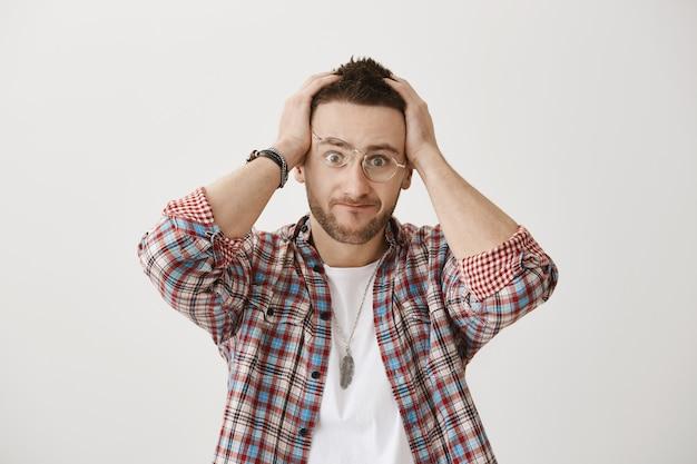 Смущенный и напряженный молодой парень в очках позирует