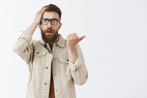 Смущенный и обеспокоенный бородатый мужчина в очках позирует на фоне белой стены