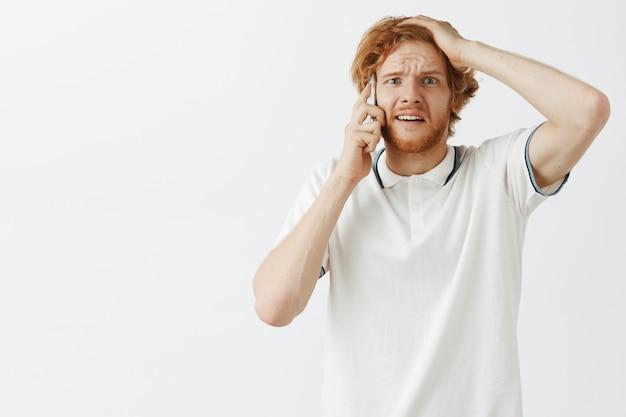混乱して心配しているひげを生やした赤毛の男が白い壁に向かってポーズ