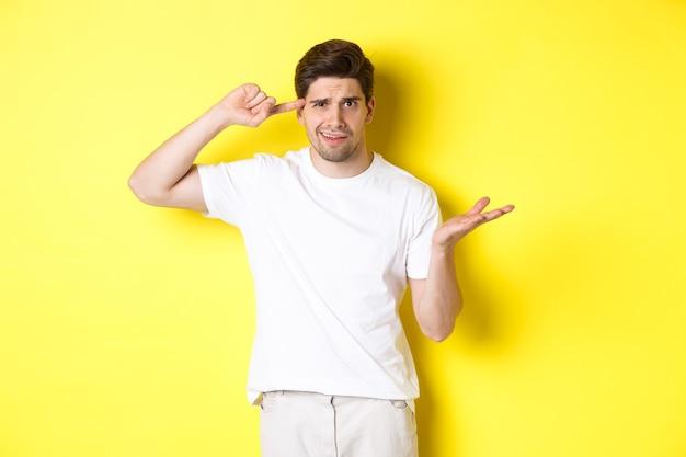 Uomo confuso e arrabbiato che punta alla testa, che rimprovera la persona per aver agito stupido, mostra un segno pazzo, in piedi su sfondo giallo.