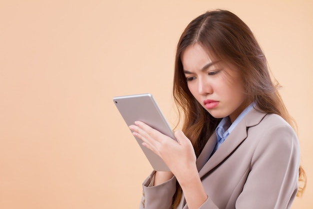 Confused asian business woman using computer tablet