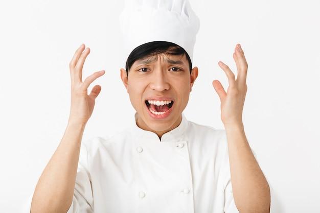 Смущенный азиатский шеф-повар в униформе, стоящий на белой стене