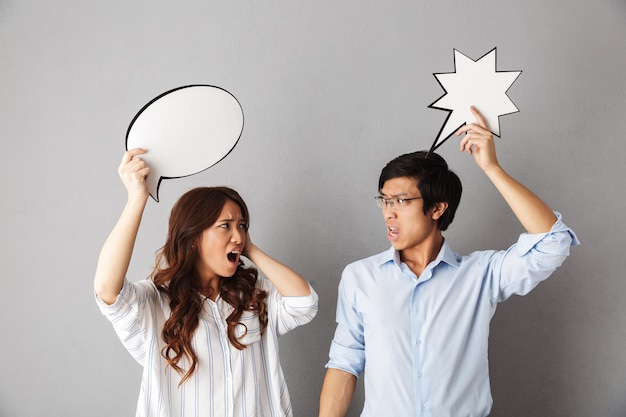Confused asian couple standing isolated, holding empty speech bubble, having an argument