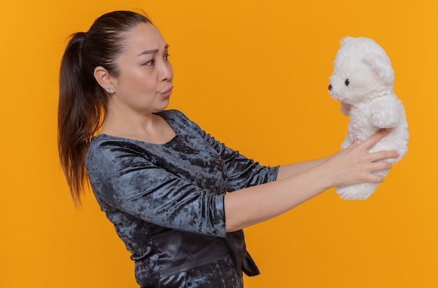 Orsacchiotto asiatico confuso della tenuta della donna che lo esamina con espressione scettica che celebra la giornata internazionale della donna in piedi sopra la parete arancione