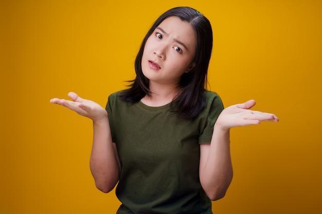 혼란 스 러 워 아시아 여자 생각 하 고 노란색 벽에 고립 된 서.