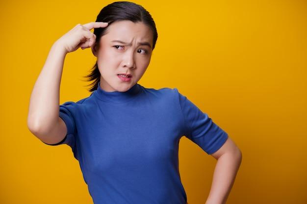 黄色に考えて立っている混乱したアジアの女性。