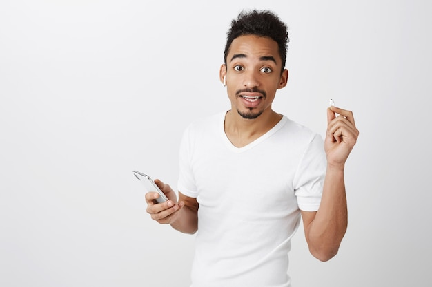 Confused attractive african american guy take-off earphone to listen, holding mobile phone, stop listening music