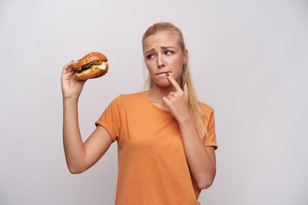 Confused attractive young blonde female in casual clothes frowning eyebrows and biting her lips while looking at big burger in her hand, counting calories and doubting, isolated white background