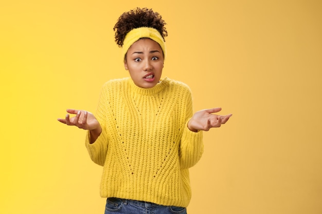 Confused awkward cute female employee messed-up papers lost paperwork shrugging raise hands uncertain say oops cringing uncomfortable standing clueless no idea what happening, yellow background.