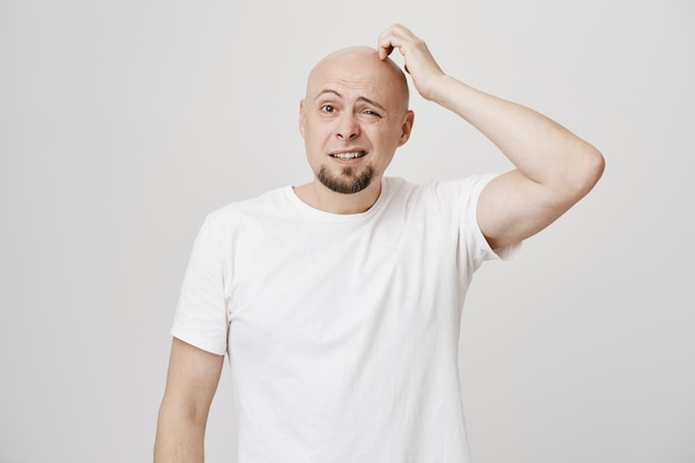 Confused bald middle-aged guy scratgh head puzzled