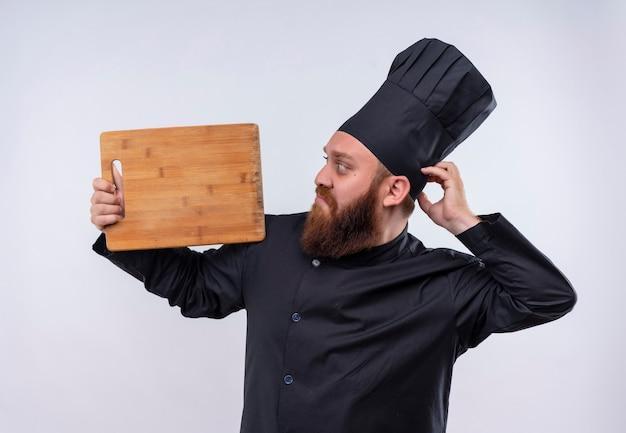 Un uomo confuso chef barbuto in uniforme nera che mostra il bordo della cucina in legno mentre lo guarda su un muro bianco