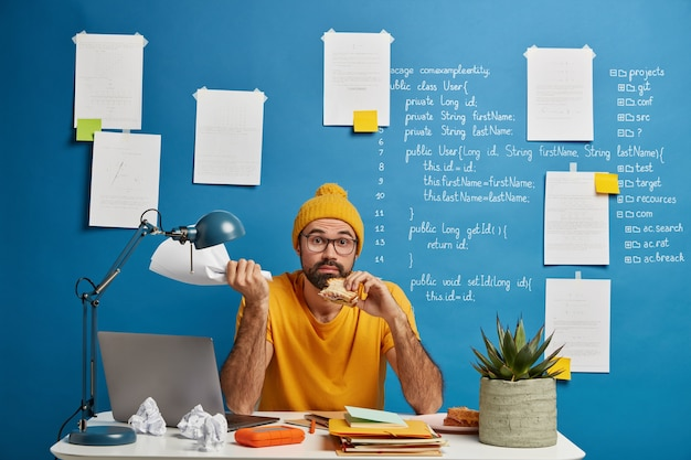Confused bearded freelance worker develops startup project, has lunch, eats delicious snack, holds paper document in hand, poses at desktop.