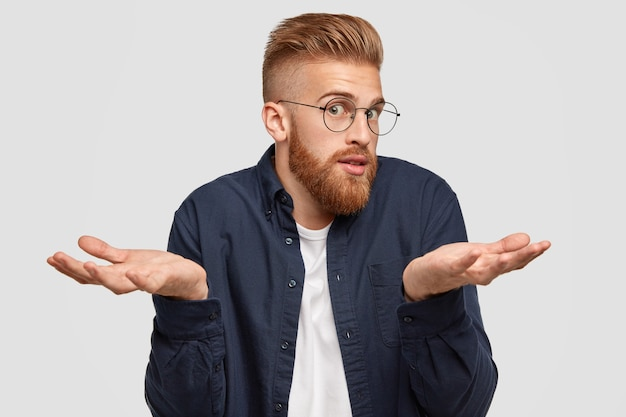 Confused bearded ginger male in spectacles looks surprisingly, shruggs shoulders with bewilderment, hesitates about something, has doubtful expression