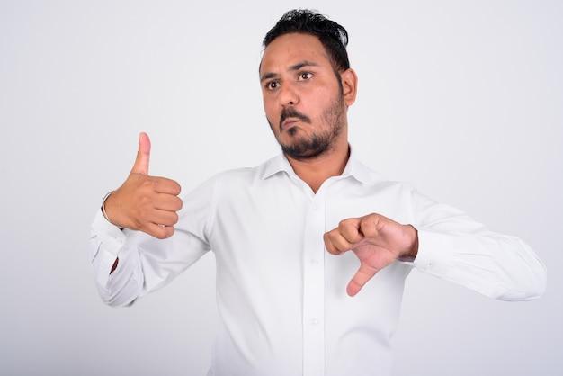 혼란 스 러 워 수염 된 인도 사업가 엄지 손가락과 아래로 엄지 손가락 사이 선택