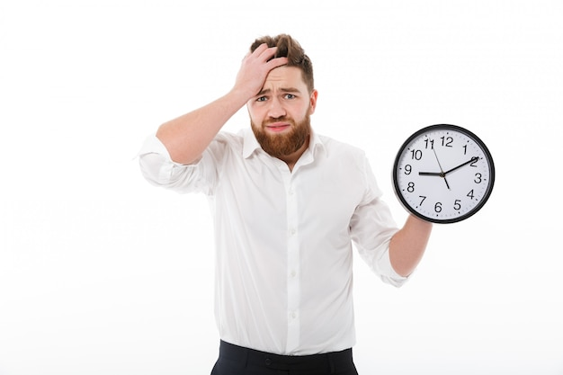 Confused bearded man in business clothes holding clock