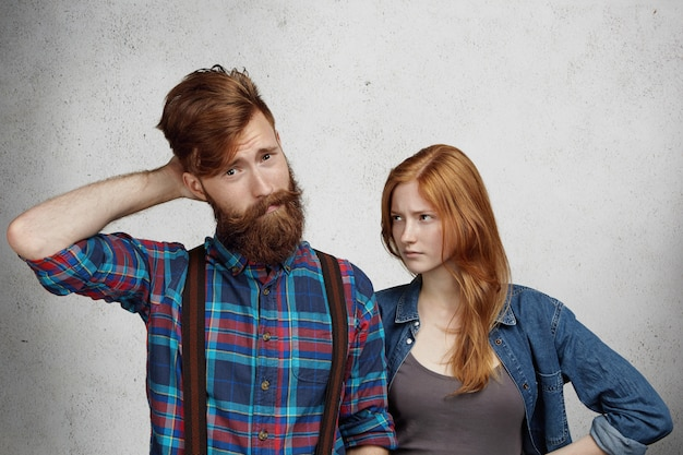 Uomo barbuto confuso che si sente in colpa, grattandosi la testa confuso mentre la sua ragazza o moglie rossa in piedi accanto a lui, guardando con espressione arrabbiata delusa, tenendosi le mani sulla sua vita