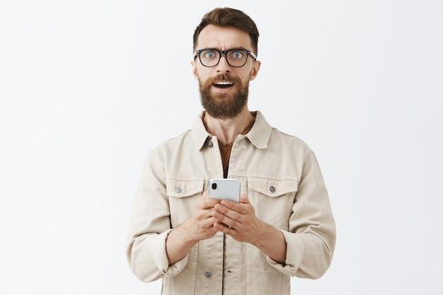 Смущенный бородатый мужчина в очках позирует у белой стены