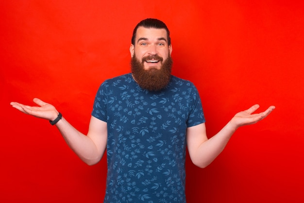 Confused bearded man is holding arms and palms open wide shrugging.