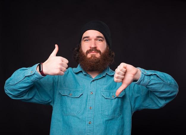 Смущенный бородатый мужчина демонстрирует жесты одновременно и нравится, и не нравится.