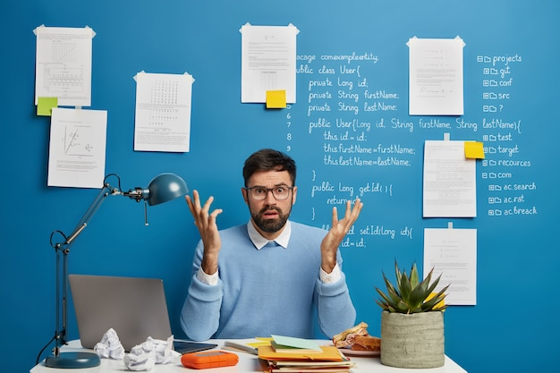 Confused bearded man raises hands with puzzlement, works freelance