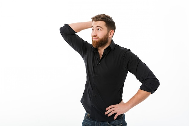 Confused bearded man in shirt holding head and looking away