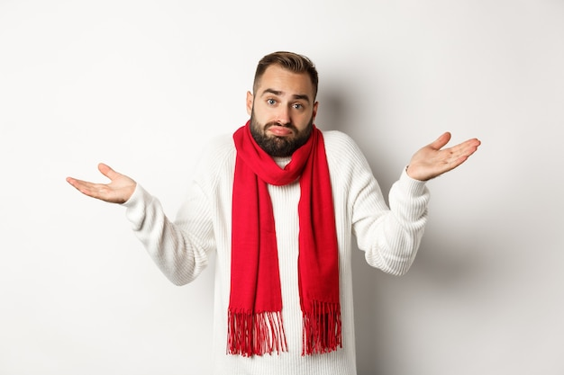 肩をすくめる、手を上げて無知に見える、何も知らない、セーターとクリスマスのスカーフに立っている、白い背景の混乱したひげを生やした男