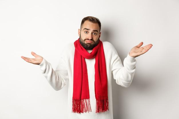 Uomo barbuto confuso che alza le spalle, alza le mani e sembra all'oscuro, non sa nulla, in piedi in maglione e sciarpa di natale, sfondo bianco